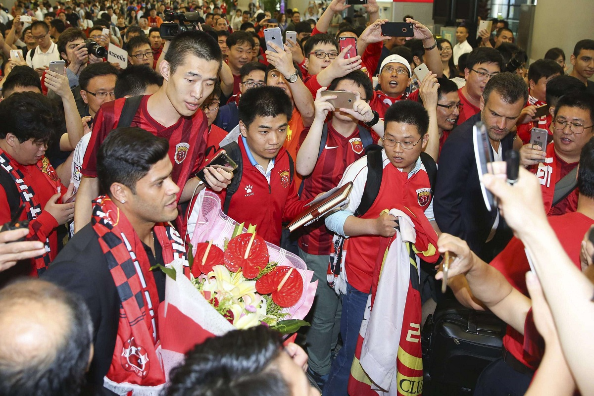 Brazilian soccer player Hulk, eft is surrounded by fans waiting at the airport in Shanghai Wednesday, June 29, 2016. Forward Hulk is expected to join Shanghai SIPG in a deal local media is predicting could be a record for the Chinese Super League. (Color China Photo via AP) CHINA OUT