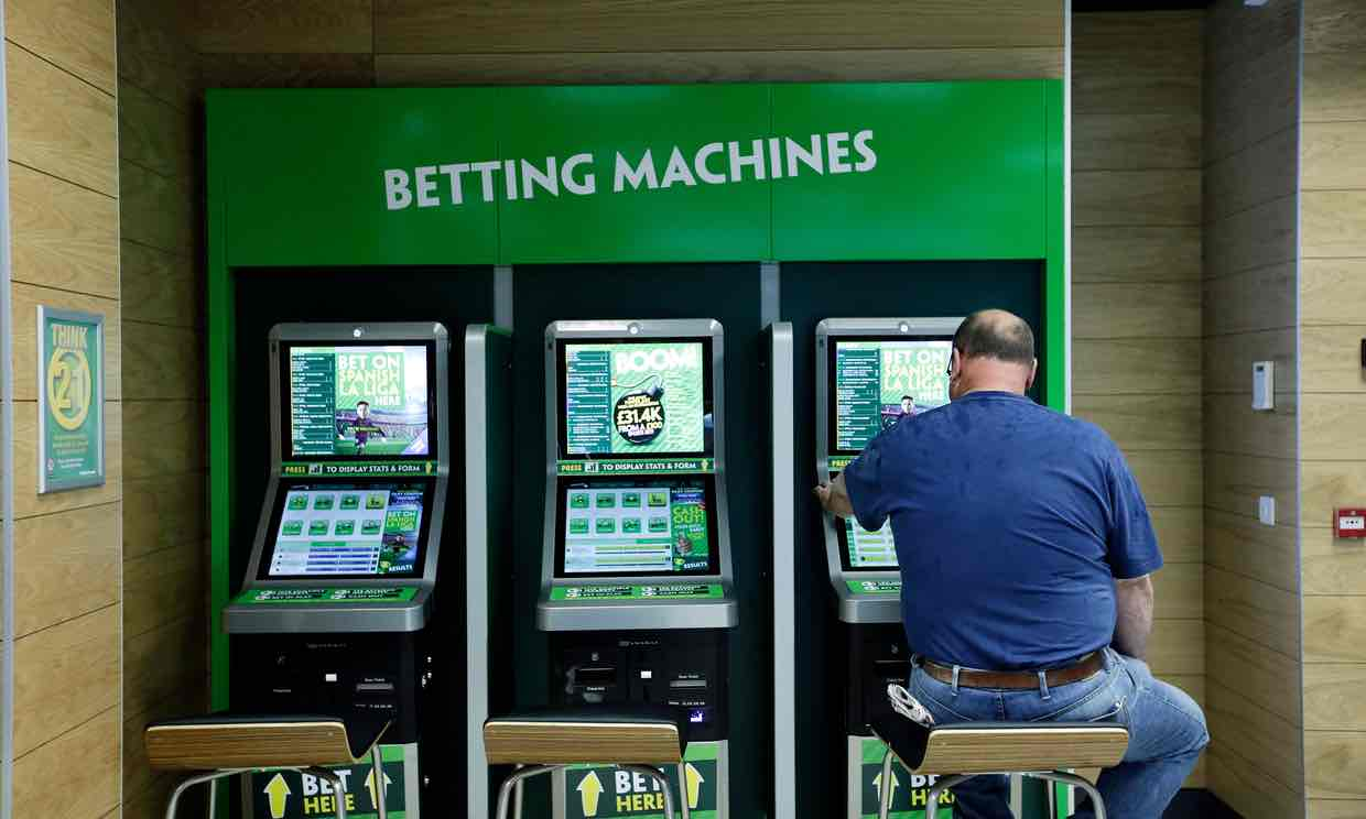 A man uses betting machines at a Paddy Power shop in London